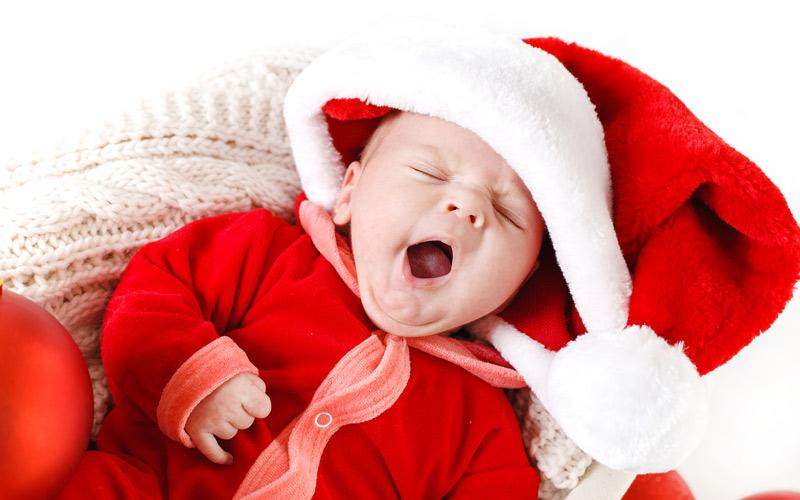 Zívajúce bábätko vo vianočnom oblečení