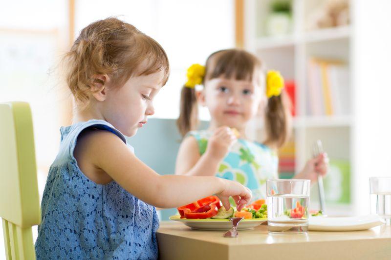 Chlapček a dievčatko jedia zeleninu