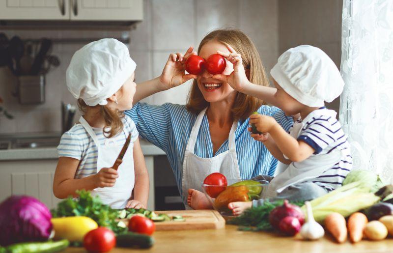 Šťastná mama sa hrá v kuchyni s deťmi